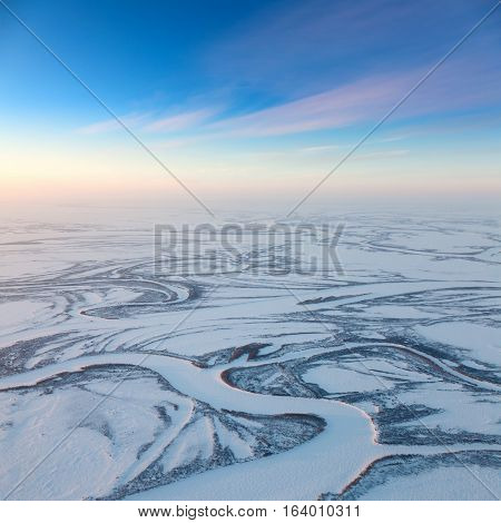 Aerial view above the endless snow covered tundra river in time of short winter day.