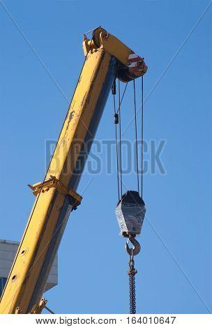 Power crane top with heavy screw over blue sky