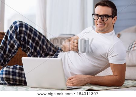 For better eyesight. Handsome pleasant delighted man working on the laptop and enjoying his tea while wearing glasses