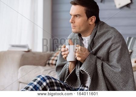 Keeping warmth. Thoughtful nice handsome man holding a cup of tea and enjoying hid drink while having a plaid on his shoulders