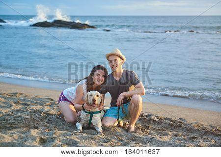 Couple with labrador dog on ocean beach sand sunset