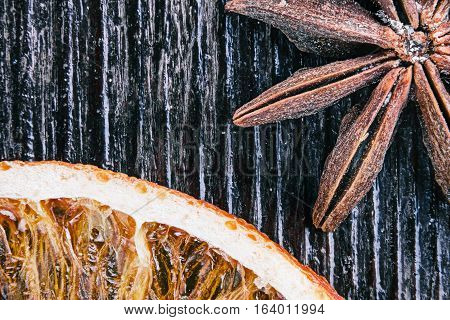 Whole star anise seed and dried orange on dark wood. Supermacro view