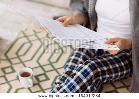 Important papers. Close up of important business documents being in hands of a self employed pleasant man while working from home