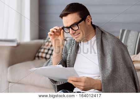 Involved in work. Good looking nice pleasant man fixing his eyeglasses and holding some documents while reviewing them