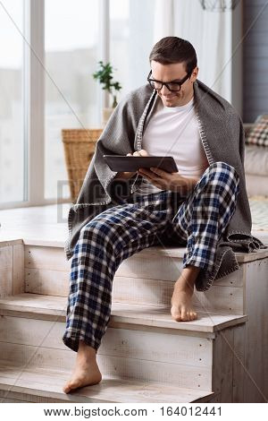 Being at home. Pleasant positive attractive man holding a tablet and working on it while sitting on the stairs