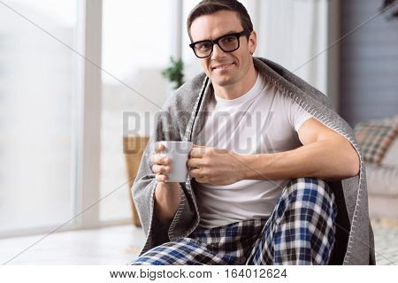 Home atmosphere. Delighted nice handsome man wearing eyeglasses and holding a porcelain cup while enjoying his tea