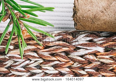 Knitted color-blend fabric  combined with milky white corduroy background with evergreen twig and cigar. Macro view