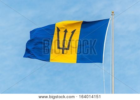 The national flag of Barbados on flagpole waving in the wind blue sky background. Patriotic symbol banner element background. Name - The Broken Trident.