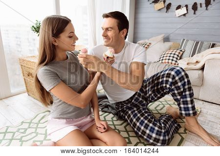 Delicious sweets. Pleasant delighted young couple giving each other cupcakes and smiling while enjoying their time together