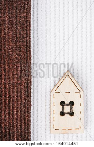 Milky white and chocolate brown corduroy combination with wood house-shaped button. Macro view. Macro view