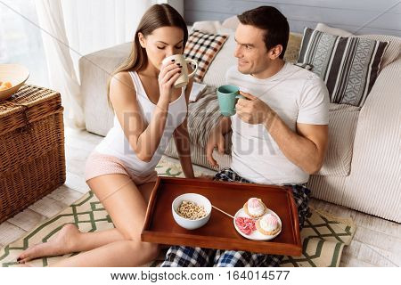 In the morning. Pleasant cute happy couple sitting together and having breakfast while having a wooden tray with food in front of them