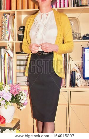 Confidently poised Woman wearing skirt and cardigan stood in office.