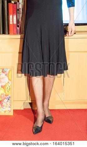 Woman wearing black skirt stood by cupboards in office