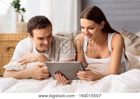 Involved in the activity. Pleasant positive cute couple lying on the bed and looking at the tablet screen while resting at home