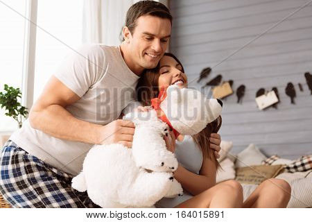 Our favourite toy. Cheerful nice young couple sitting together and hugging a stuffed toy while enjoying their time together