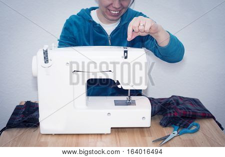 Woman arrange thread from the spool on the sewing machine