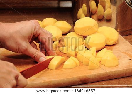 Potato, knife and hands and wooden plank