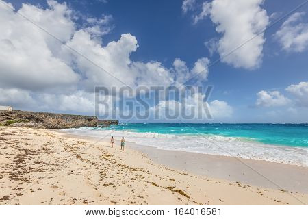 Bottom Bay Barbados - December 18 2016: Couple relaxing on the Bottom Bay beach Barbados Caribbean. Vacation background.