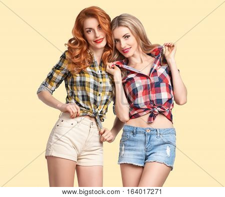 Fashion woman Having Fun Crazy Cheeky Dance. Hipster Sisters Best Friends Twins in Stylish Summer Outfit. Funny Model Girl Fashion Plaid Shirt.Glamour fashion Trendy Hairstyle, dancing. Creative