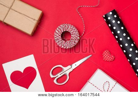 Packing holiday gifts for Valentine's day on red background.