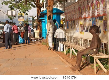 UGANDA, KAMPALA- MARCH 17: Homeless ill boy sits on a bench of bus stop, March 17, 2006 in Kampala, Uganda. Social issue of poor African countries.