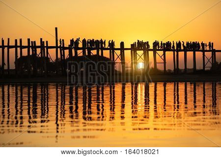 Silhouette of people traveling across the U Bein Bridge in the evening. Mandalay Myanmar