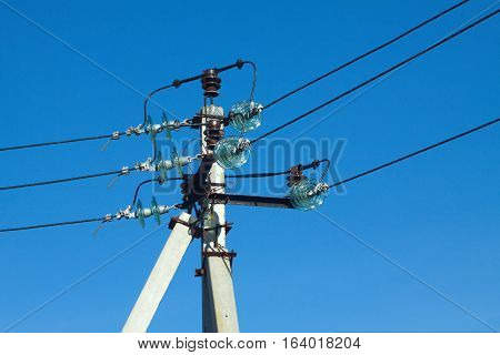 Concrete electric pole of power supply line with wires over clear cloudless blue sky