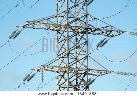 Mid section of high-voltage power line grey metal support with many wires over clear cloudless blue sky