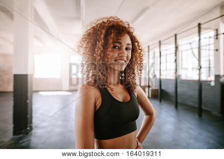 Portrait of smiling young african woman with curly hair in health club. Happy and beautiful fitness woman at gym.