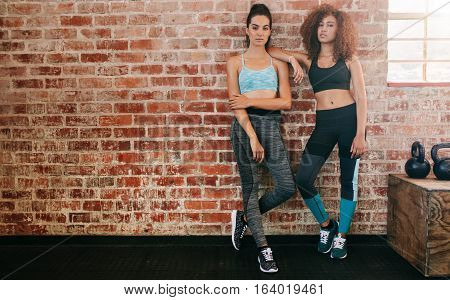 Full length shot of two young women standing by wall in gym. Fitness females relaxing at workout.