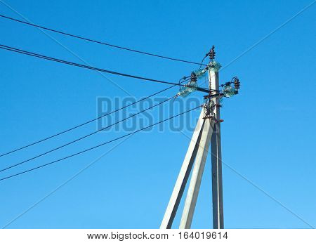 Support of rural power lines over clear cloudless blue sky in summer day