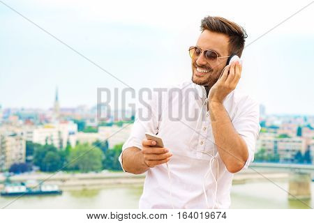Portrait of smiling young man.Young man listening to music on a smart phone.