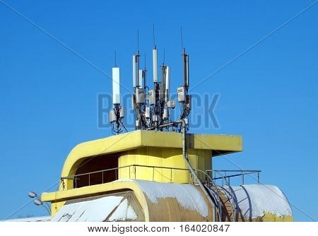Many electronics aerials on yellow building top over blue cloudless sky
