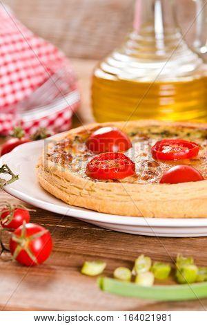 Leek and tomato quiche on white dish.