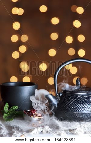 Smoking hot tea in black ceramic pot with black cup front of bokeh background