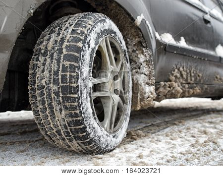 Detail of car. Tire standing on winter road with snow