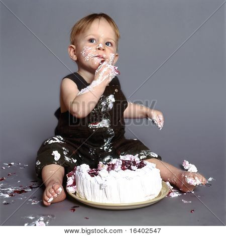 Cute little boy eating his first birthday cake