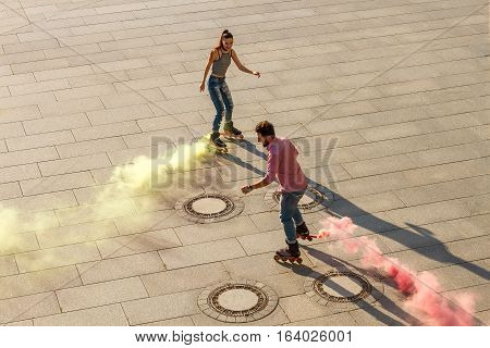 Couple is rollerskating. Colorful smoke coming from rollerskates. Colorize the world.