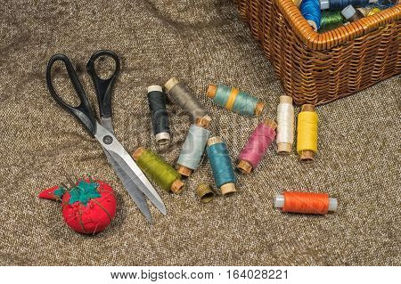 Sewing tools and accessories on fabric background. Sewing kit. Thread on bobbins, scissors, needles, thimble and sewing box.