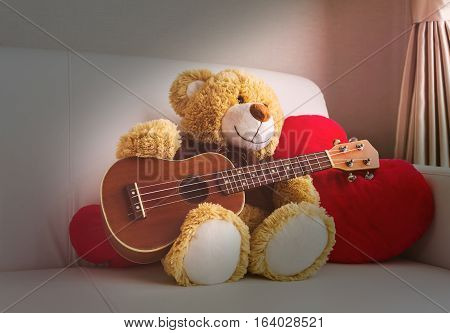 Cute bear doll with ukulele on sofa in love mood