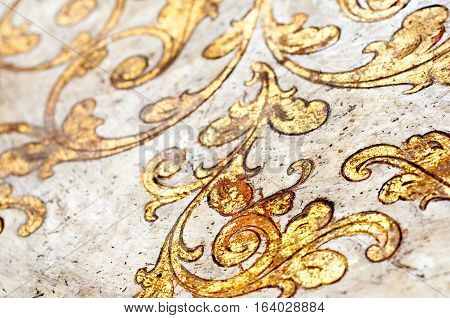 Flourish pattern. Gold leaf floral design on white background. Old antique surface.