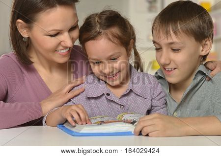 mother learning lessons with kids, reading a book