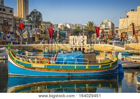 St.Julian's Malta - Traditional colorful Luzzu fishing boat at Spinola bay at sunrise