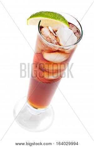 Cocktail with cola ice cubes in a tall glass garnished slice of lime. Isolated on white background.