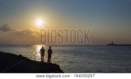 Valletta Malta - Early in the morning two fishermen are waiting for a bite at Sliema Tigné point with Breakwater Lighthouse at background