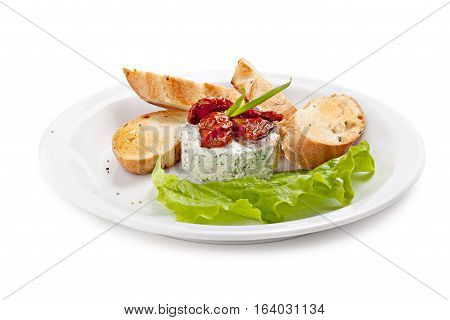 Ricotta salad decorated with sun-dried tomatoes and lettuce served with croutons isolated on white background.