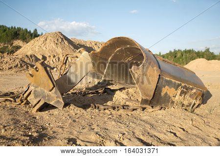 Broken big heavy bucket lies on sand on summer day before forest. Horizontal photo closeup