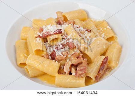 Close-up italian rigatoni plate with prosciutto parmesan cheese