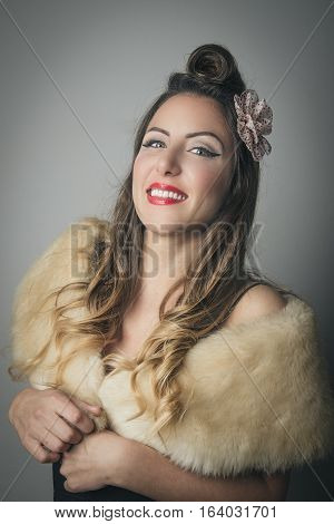 Upper body portrait of smiling young woman with fur wrap around shoulders studio background