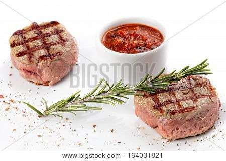 Filet mgnon medium rare served with saucedecorated with sprig of rosemary and spices